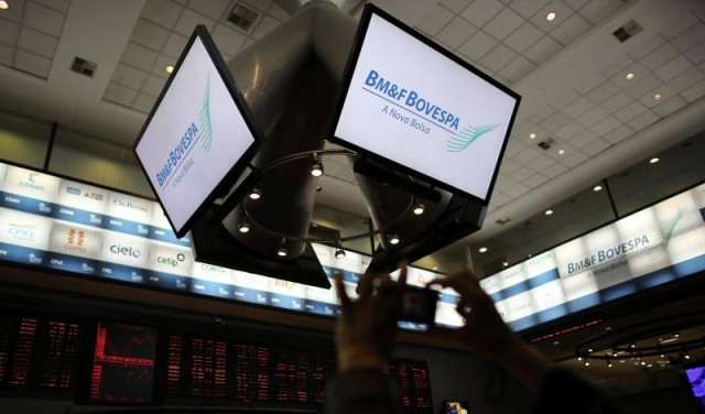 A woman takes a picture of an electronic display board at Brazil's BM&FBovespa stock exchange in Sao Paulo October 7, 2013.  REUTERS/Nacho Doce