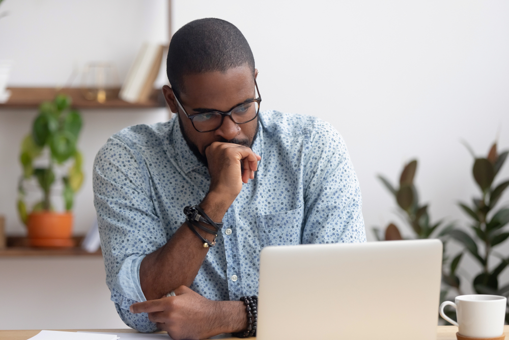 Head,Shot,Serious,Puzzled,African,American,Businessman,Looking,At,Laptop