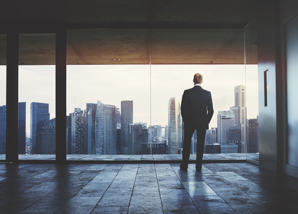 Businessman,Looking,At,City,Through,Window