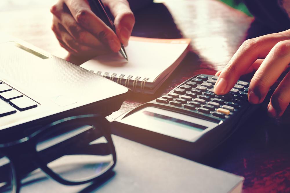 Close,Up,Woman,Hand,Using,Calculator,And,Writing,Make,Note