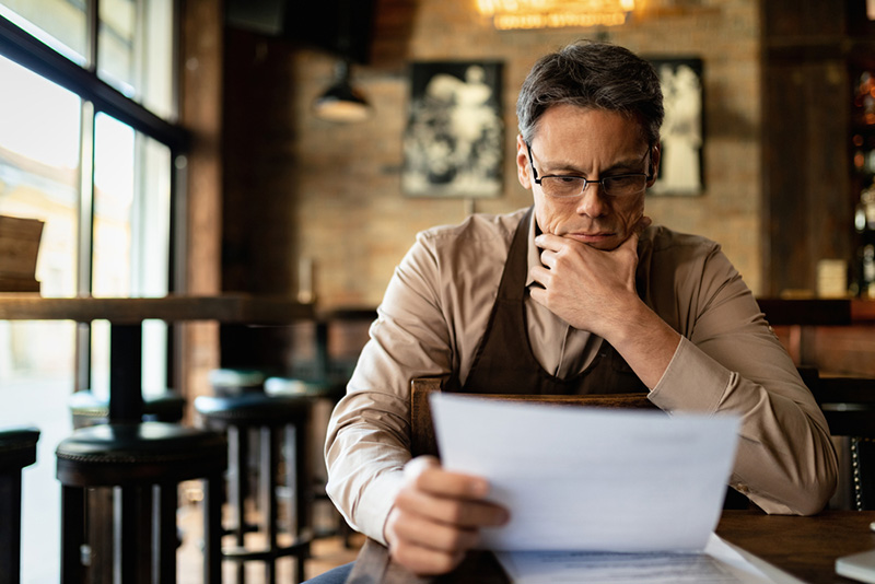 Pensive cafe owner reading going through paperwork and reading reports after working hours.